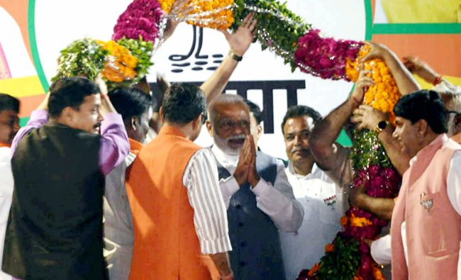 Prime Minister Narendra Modi being garlanded at an election rally in Varanasi...