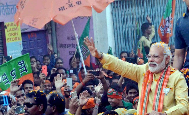 Prime Minister Narendra Modi waves to people during his road show in Varanasi...