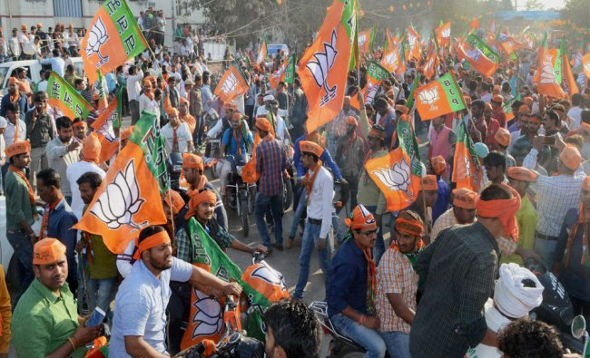 Supporters wave flags at the second road show of Prime Minister Narendra Modi in Varanasi...