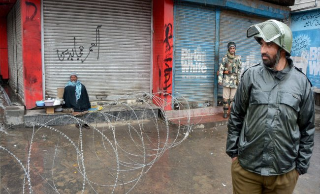 Security personnel guard as an elderly street vendor waits for customers at a blocked road...