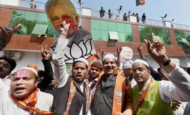 BJP supporters celebrate as early trends show the party\'s win in the Uttar Pradesh and Uttarakhand..