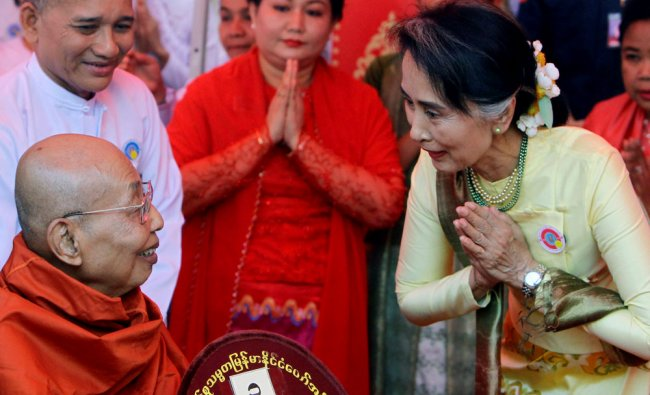 Myanmar State Counsellor and Foreign Minister Aung San Suu kyi, right, pays respect to a monk...