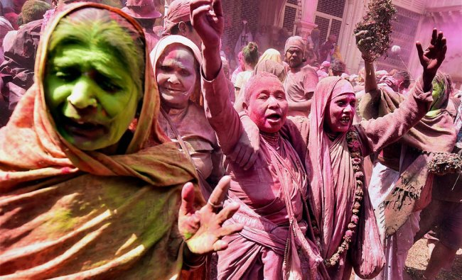 Widows playing Holi with colours at ancient Gopinath Temple in Vrindavan...