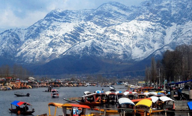 Tourists taking shikara ride on a sunny day after five days of rains and snow, at Dal Lake...