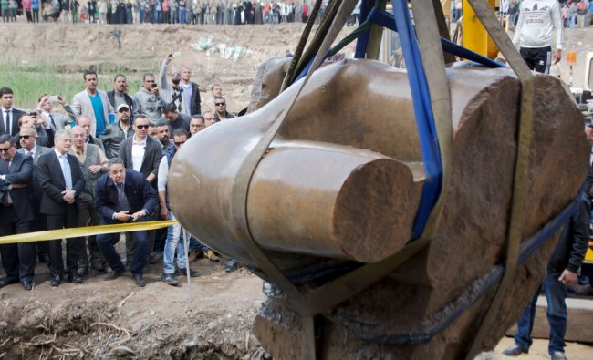 Antiquities officials watch a massive statue, that may be of pharaoh Ramses II...
