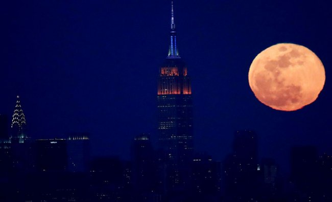 The full moon rises behind the New York City skyline, including the Empire State Building...
