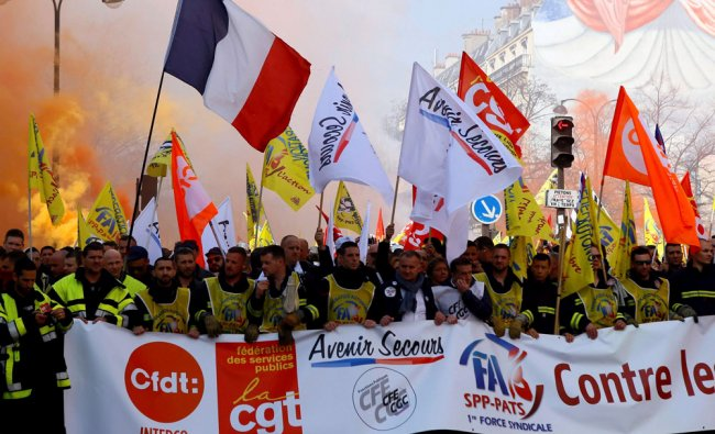 Firefighters from different region of France carrying a french flag, at left, and a banner attend...