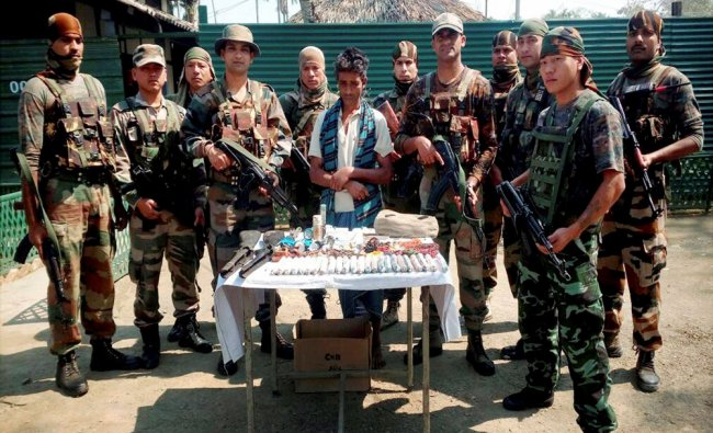 Assam Rifles men showing IEDs and other explosives recovered from a weapons dealer...