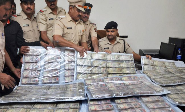 Police personnel display seized old currency notes of 1000 and 500 at Kherwadi police station in ...
