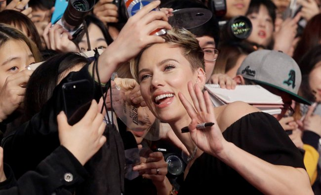 Actress Scarlett Johansson poses with fans for a selfie during a promotional event for her latest...
