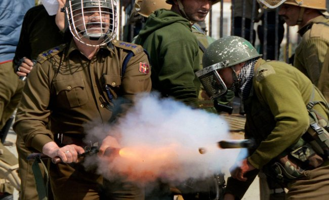 A police officer fires teargas shell to disperse stone throwing youths during a clash in Srinagar...