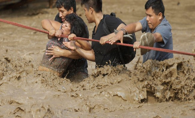 A group of people, stranded in flood waters, hold onto a rope as they wade through flood waters...