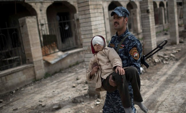 A Federal Police officer carries an injured boy through a destroyed train station during...