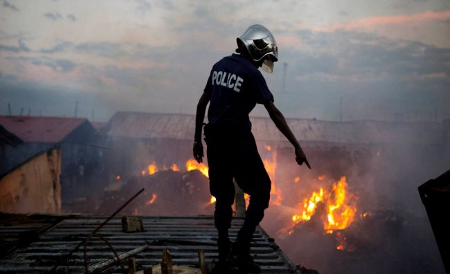 A firefighter points as he works to extinguish a massive fire at a market in Port-au-Prince...