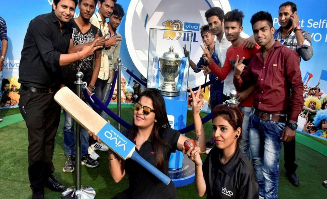 Cricket fans pose with the IPL trophy during its tour in the Patna on Monday...