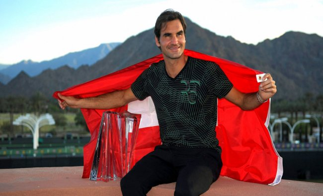 Roger Federer, of Switzerland, poses with his trophy and the Swiss flag after defeating Stan...
