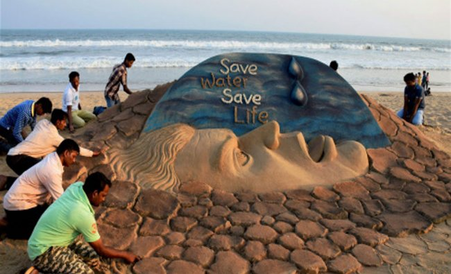 Students of Sand Art School creates a sand sculpture on World Water Day at Puri beach of Odisha