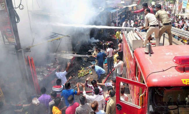 Fire personnel dousing a major fire that broke out in the shops outside Mahakaleshwar temple...