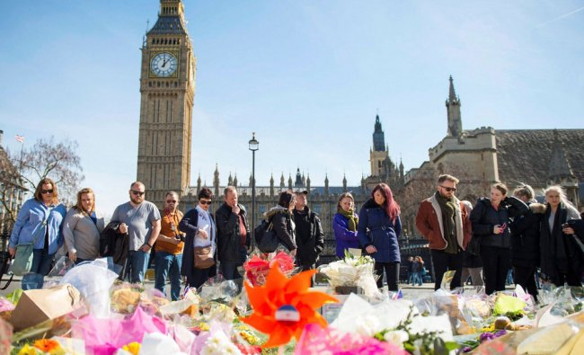 People look at floral tributes in Parliament Square, London, Sunday, March 26, 2017, laid out...