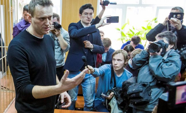 Russian opposition leader Alexei Navalny, foreground, speaks to press in a court room in Moscow....
