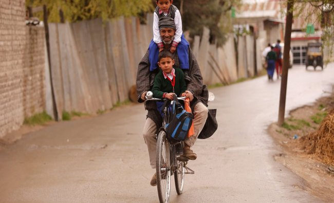 A man carries schoolchildren on his bicycle on a road in Srinagar, India...