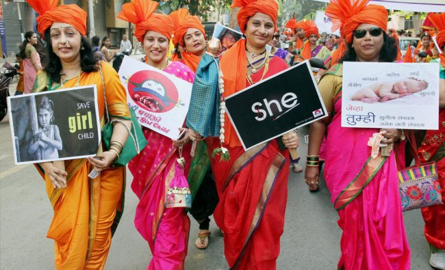 A group of Marathi women, dressed in traditional attires, with placards displaying...