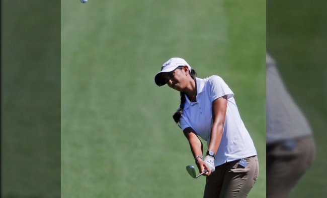 Aditi Ashok, of India, chips to the green on the first hole during the third round of the LPGA...