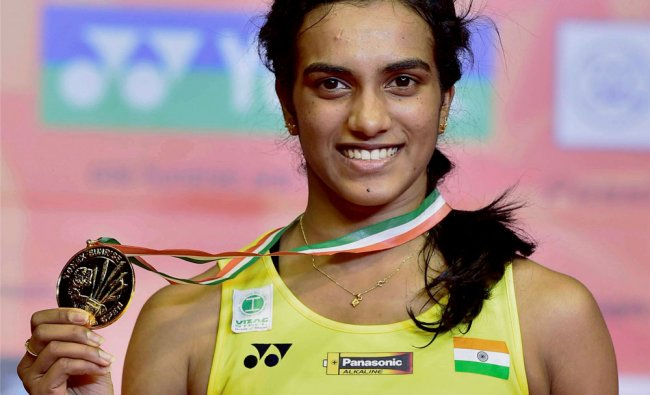 Indias P V Sindhu is all smiles as she poses with her medal and trophy...