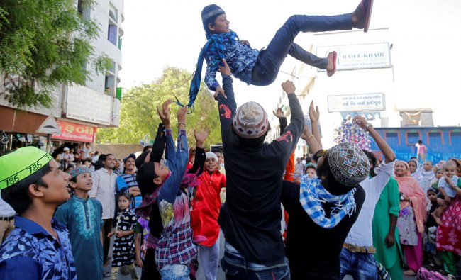 A performer is thrown into the air by Muslim devotees during an annual religious procession...