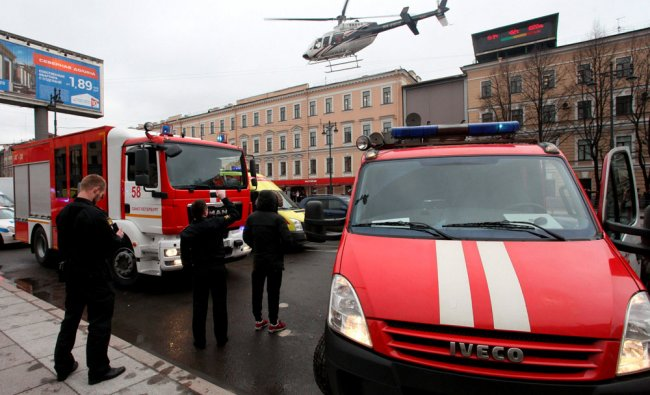 A helicopter flies over the fire trucks after an explosion at Tekhnologichesky Institut subway...