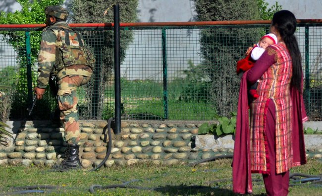 A woman with her child looks on as an army jawan searching the lawans of her house after militants..