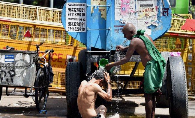 A Tamil farmer helps a disabled man take a bath, as farmers from Tamil Nadu protest demanding loan..