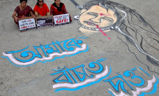 Demonstrators hold placards as they sit next to a mural during a protest against rape incidents...