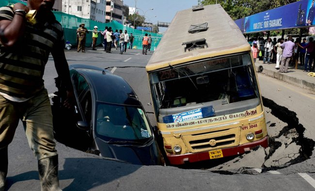 A car and a Metropolitian Transport Corporation (MTC) bus sink into a huge crater formed after...