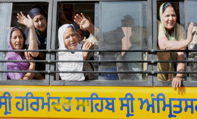 Sikh wave from a bus as they leave to board a special Pakistan-bound pilgrimage train to celebrate..