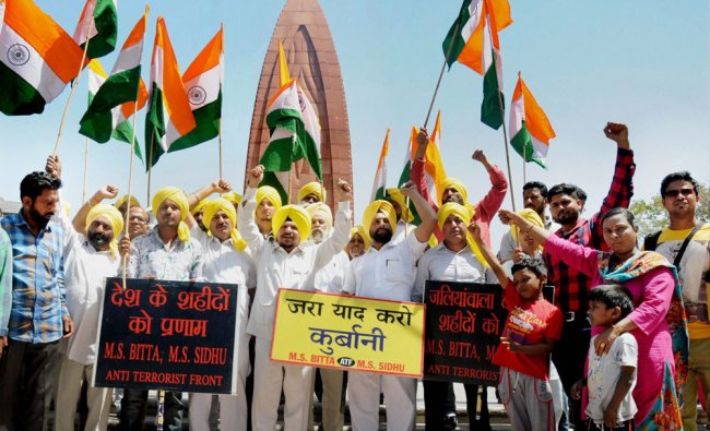 Activists of All India Anti Terrorist Front (AIATF) hold national flags as they shout patriotic ...