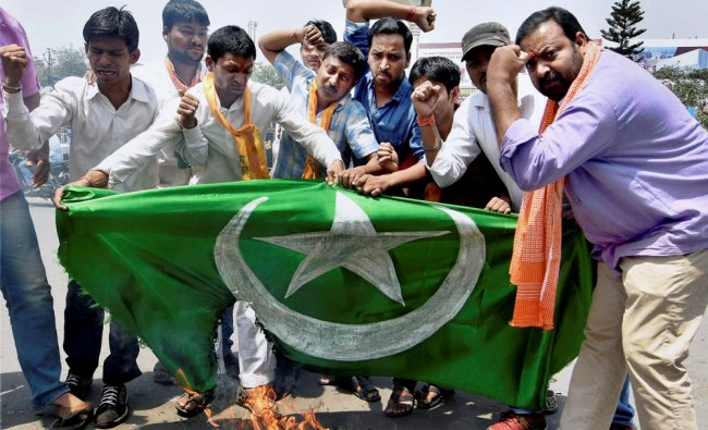 BJP activists burn the Pakistani flag during their protest against the death sentence awarded to ...