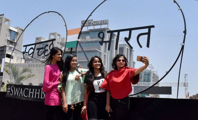 Girls take selfie with a promotional board for \'Swachh Bharat\', before PM Narendra Modi\'s visit...