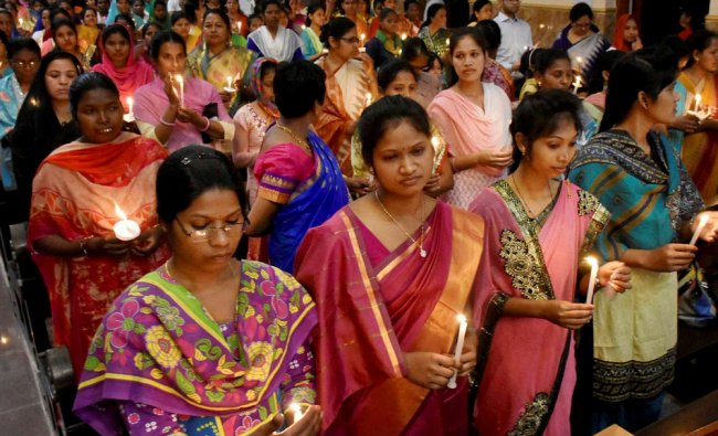 Christian devotees offer prayers in a midnight mass candle light vigil on the occasion of Easter ...