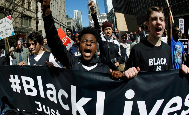 Bryce Green, 12, center, takes part in a Black Lives Matter protest march with his friend Danilo ...