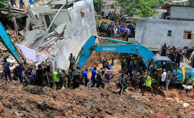 Sri Lankan government soldiers and rescue workers cary a body recovered from site of a garbage ...