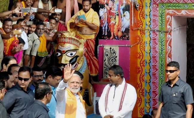 Prime minister Narendra Modi waves at people during his visit to Lord Lingaraj temple in Bhubaneswar