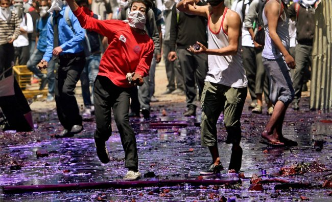 Students pelt stones at security forces during a clash in Srinagar