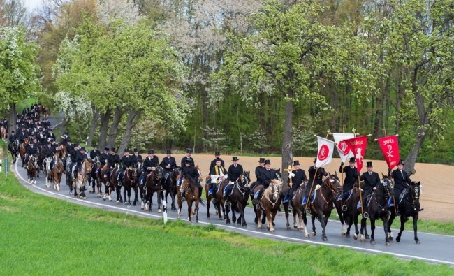 Sorbian men dressed in black tailcoats ride decorated horses during Easter