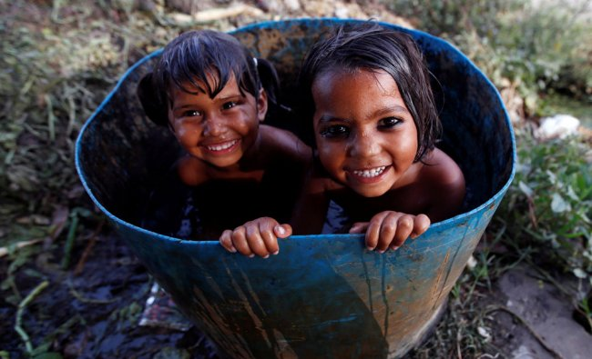 Girls bath inside a drum on a hot summer day at a field in New Delhi...
