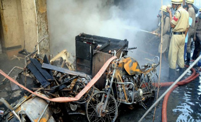 Firemen spray water after fire broke out at crackers shop in Indore...