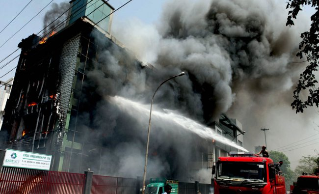 Firefighters douse a fire theat broke out in a factory in Noida...