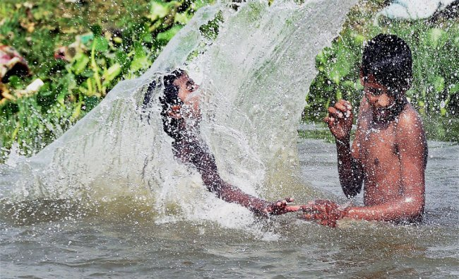 Children taking a bath to beat the heat in hot afternoon in Gomti river in Lucknow...