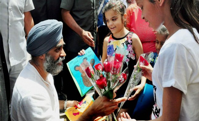 Canadian Defence Minister Harjit Singh Sajjan being greeted by children during his visit...