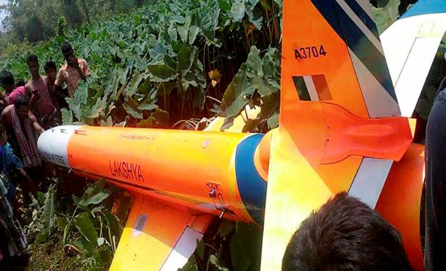 People gather near the missile Lakshya, the advanced Unmanned Aerial Vehicle (UAV) that crashed...